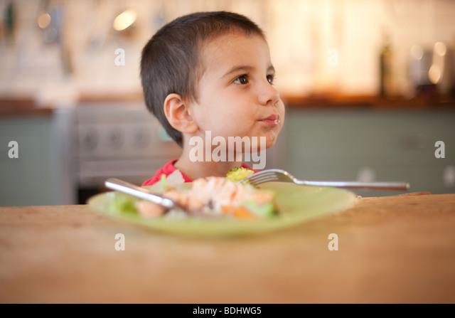 Junge sitzt nicht essen einen Teller mit Essen Stockbild