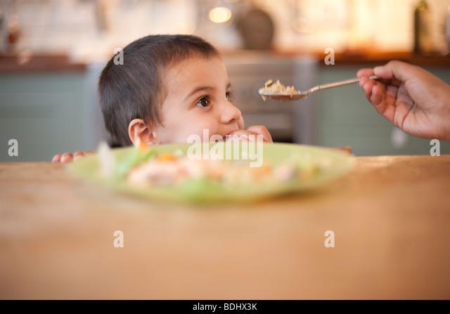 3 Jahre alter Junge sitzt am Tisch mit Hand Essen auf Löffel Stockbild