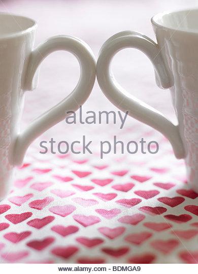 Nahaufnahme von zwei Kaffeetassen auf Tischdecke mit Herzen dekoriert Stockbild