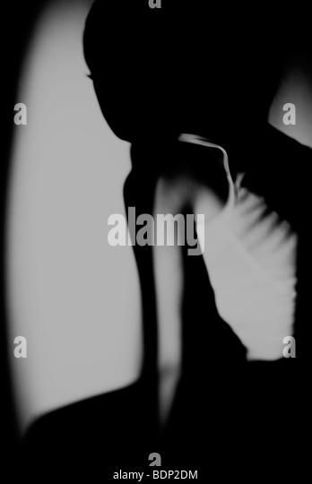 Eine junge Frau sitzt im Schatten Stockbild