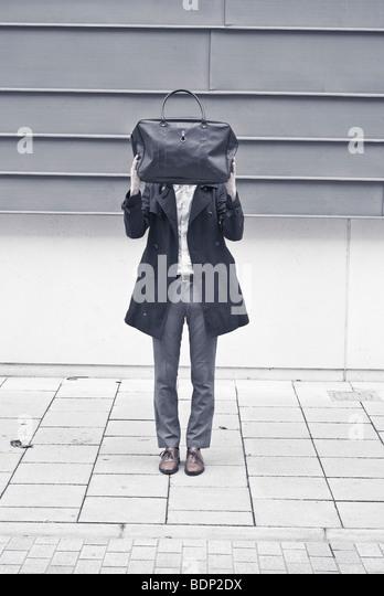 Ein Mann steht auf einer Straße versteckt sich hinter einer Tasche Stockbild