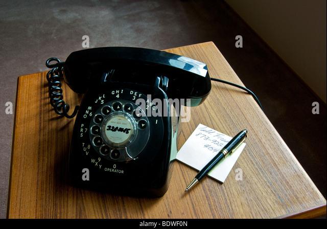Veraltete Technik alte schwarze Rotary Durchwahltelefon auf Teak Beistelltisch Stockbild