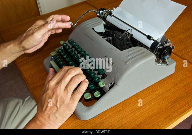 Veraltete Technik manuelle Reiseschreibmaschine Finger schieben auf Schlitten zurück, Papier auf Trommel zu Stockbild