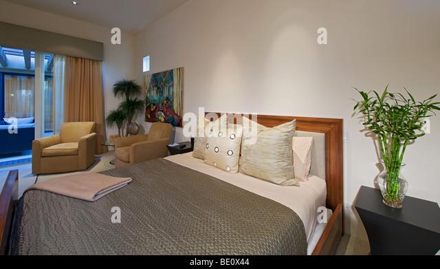 Zeitgenössische Teakholz Bett mit eleganter Bettwäsche und gepolsterten Stühlen im Hintergrund durch Stockbild