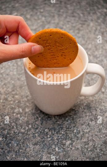 Eine Nahaufnahme einer Person ein Toffifees Verdauungs Keks in einer Tasse Tee Eintunken Stockbild