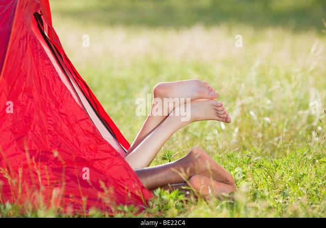 multiethnische Pärchen im Zelt mit Füßen liegend überquerte. Textfreiraum Stockbild