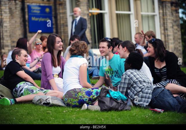 Studenten entspannen auf dem Rasen während einer Pause an einem Sixth Form College, fort-und Weiterbildung Stockbild
