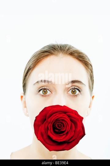Porträt der jungen Frau mit einer Rose im Mund Stockbild