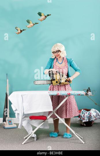 Retro-Hausfrau, die unter einer Kettensäge zu ihrem Bügelbrett Stockbild