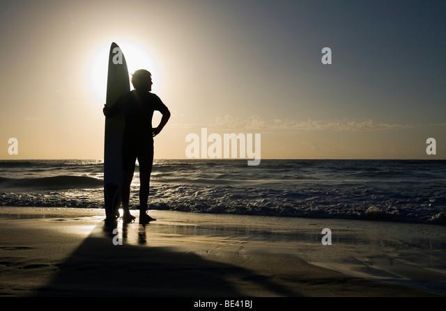 Mann, stehend mit Surfbrett bei Sonnenaufgang.  Bondi Beach. Sydney, New South Wales, Australien Stockbild