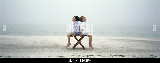 Zwei Jungs sitzen Rücken an Rücken auf Stuhl am Strand Stockbild