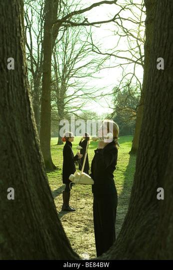 Frauen stehen im Freien, mit Festnetz-Telefone, angezeigt durch Baumstämme Stockbild