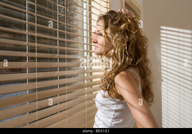 Neugierige Frau im Schlafzimmer spähte durch Jalousien morgens Stockbild
