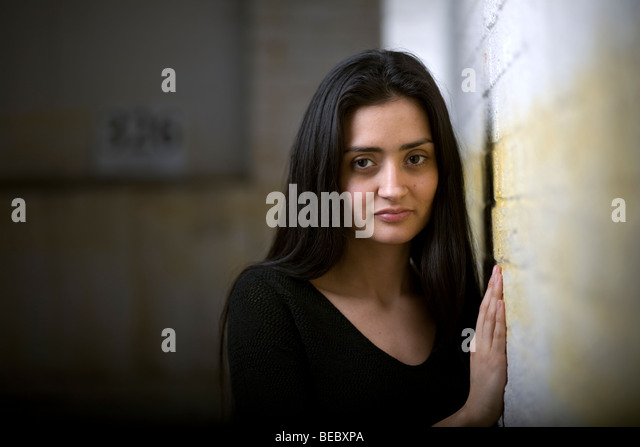 Eine hübsche Latein oder Spanisch Frau an eine Wand gelehnt. Stockbild