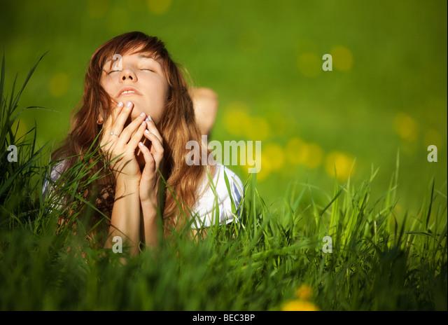 Junge Frau auf dem Rasen liegen. Flachen Dof. Stockbild