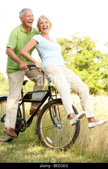 Älteres Paar Reiten Fahrrad in Landschaft Stockbild