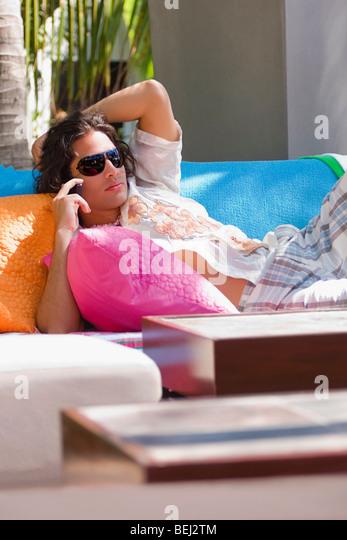 Junger Mann auf einer Couch liegen und telefonieren mit dem Handy Stockbild