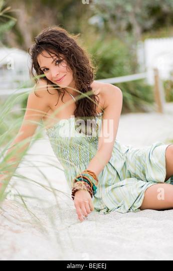 Porträt einer jungen Frau am Strand sitzen und Lächeln Stockbild