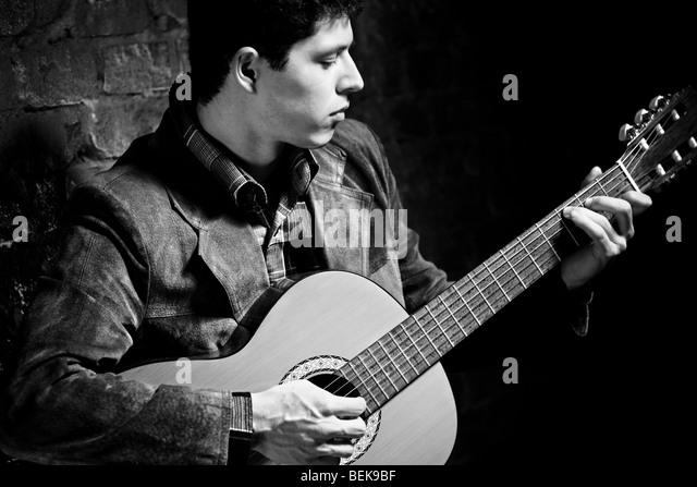 Junger Mann an der Gitarre zu spielen. Dunkle Farben schwarz und weiß. Stockbild