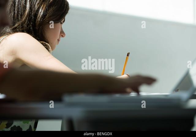 Teenager-Mädchen schreiben am Schreibtisch Stockbild