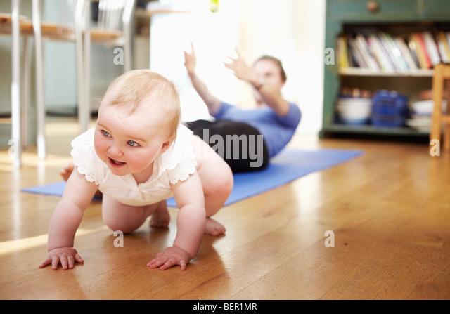 Mutter mit einem Baby Yoga machen Stockbild