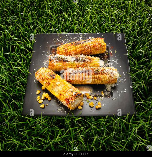Gegrillte Maiskolben mit Käse, Butter und Chili auf einem Rasen-Hintergrund. Stockbild