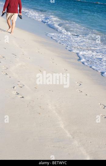 männliche Senioren zu Fuß an einem Sandstrand mit seinen Sandalen, Morgenspaziergang Stockbild