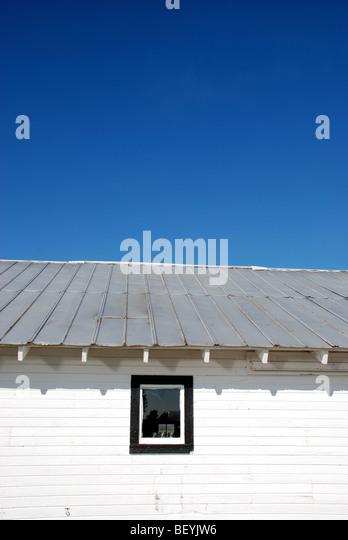 Weiße Scheune unter blauem Himmel Stockbild