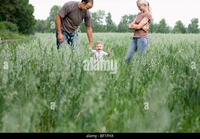 Zwei Eltern spielen mit ihrer Tochter in einem Feld Stockbild