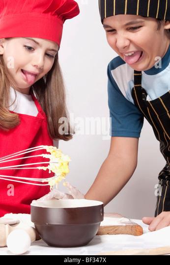 Junge mit seiner Schwester mit Abscheu auf die rohe Mischung aus Kuchen Stockbild