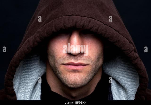 Eine böse aussehenden Mann trug ein Kapuze-Top mit seinen Augen verborgen vor einem schwarzen Hintergrund. Stockbild