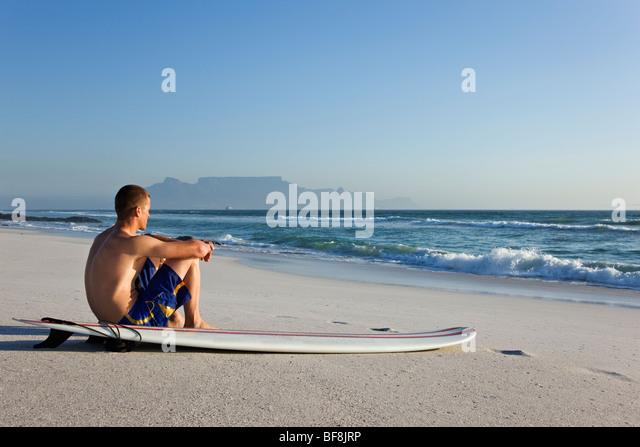Surfer am Strand von Bloubergstrand mit dem Tafelberg im Hintergrund. Kapstadt-Südafrika Stockbild
