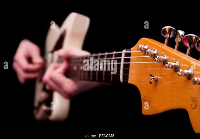 Electric jazz Akustikgitarre mit unscharfen Händen gespielt wird, isoliert auf schwarz. Stockbild