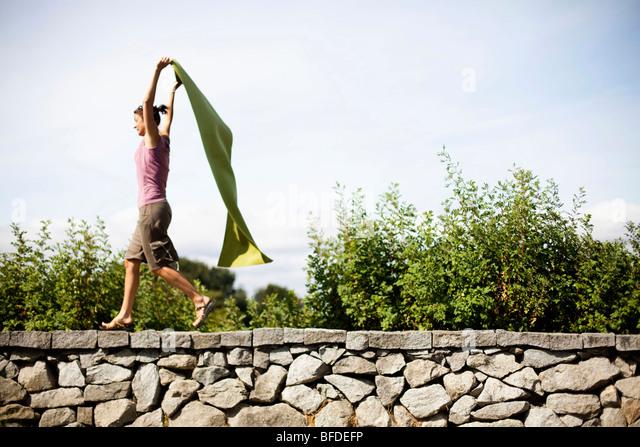 Eine Frau behauptet, ihre grüne Yogamatte einen Umhang ist beim laufen auf einem Stein Felsvorsprung. Stockbild