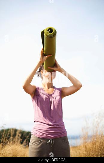 Eine junge Frau sieht spielerisch durch ihre Yoga-Matte, handeln, wie es ein Teleskop ist. Stockbild