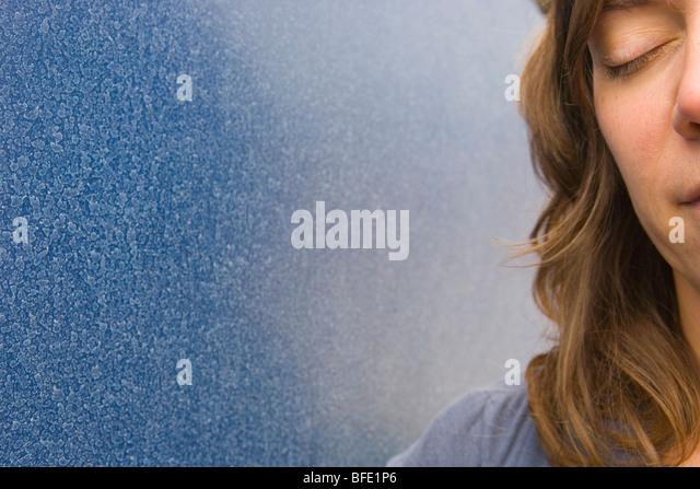 Nahaufnahme von Frau mit Augen geschlossen neben blauen Wand Stockbild