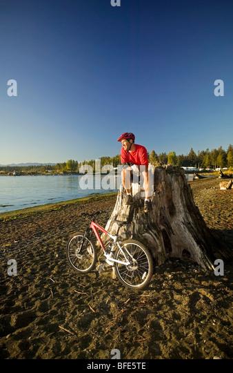 Mountainbiker, entspannen und genießen der Aussicht von Georgia Strait, Black Creek, Vancouver Island, British Stockbild