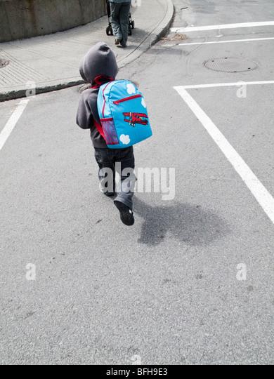 3,5 Jahre alten eurasischen junge mit einem Rucksack die Straße überqueren Stockbild