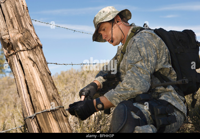 Soldat schneiden Stacheldrahtzaun Stockbild