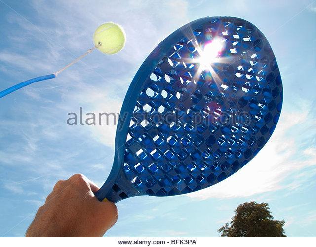 Sonne hinter Paddel Tennisball schlagen Stockbild