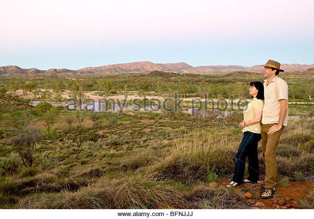 Ein paar in ihren 30ern Umarmung beim Blick auf das MacDonnell Ranges Stockbild