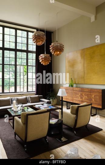 Wohnzimmer mit Artischocke Lichter, große Fenster und Kunstwerke. Stockbild