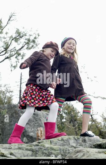 Schwestern zu Fuß auf felsigen Seeufer Stockbild