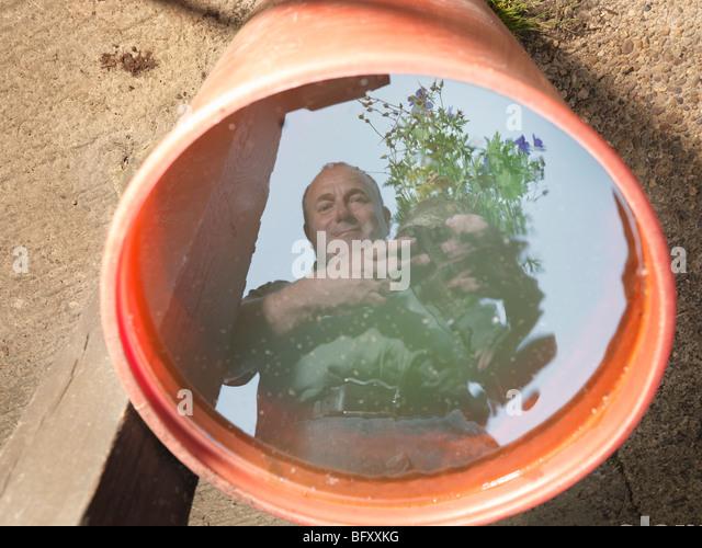 Reflexion der Gärtner im Wasser Stockbild