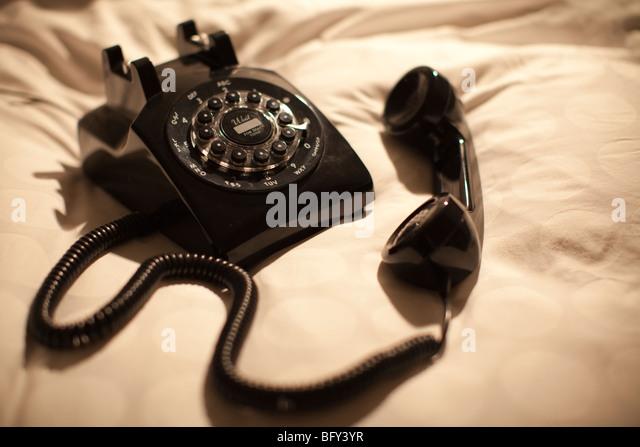 Schwarze alte Mode Telefon links abgehoben auf Bett Stockbild