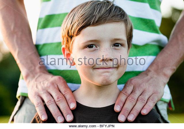 Vater mit den Händen auf den Schultern der Söhne Stockbild