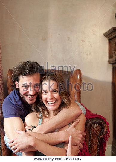 paar in alten Stuhl umarmt, lachen Stockbild
