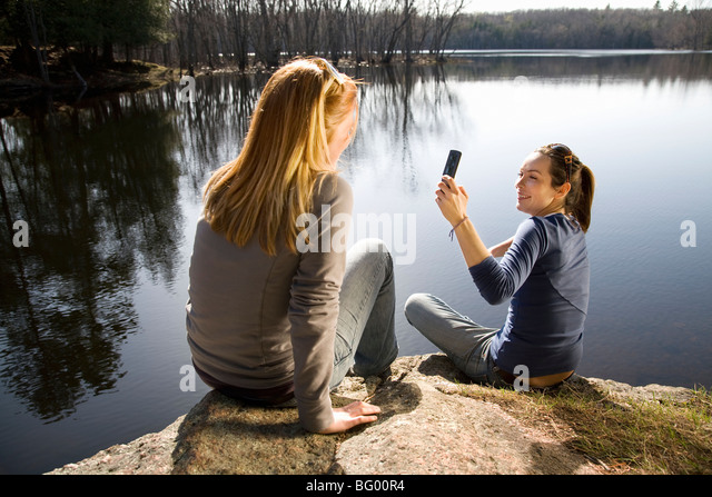 Zwei Frauen, die Aufnahme mit Handy Stockbild