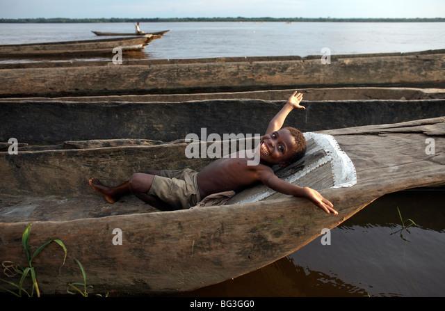 Ein Junge entspannt in einem Einbaum-Kanu auf der Kongo-Fluss, Yangambi, demokratische Republik Kongo, Afrika Stockbild