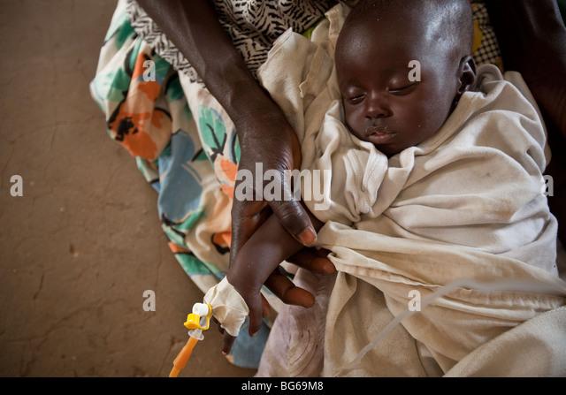 Eine Mutter hält ihr Kind, leidet unter Dehydratisierung in einem Krankenhaus in Amuria, Uganda. Stockbild
